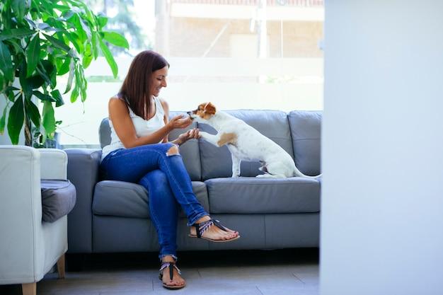 Donna in un divano con un cucciolo allegro
