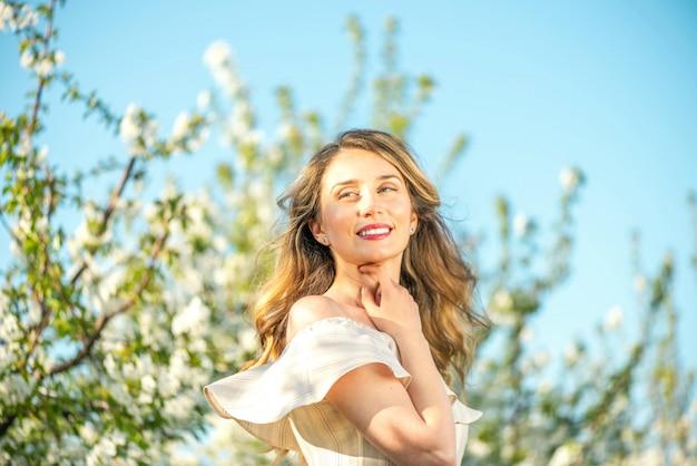 Donna in un frutteto di ciliegio in fiore in primavera