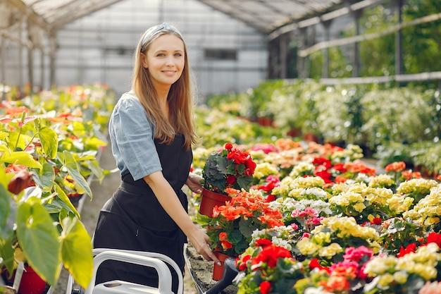 Donna in un grembiule nero che lavora in una serra