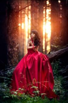 Donna in un lungo abito rosso da solo nella foresta
