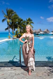 Donna in un lungo prendisole prima della piscina a sfioro, con vista sul mare