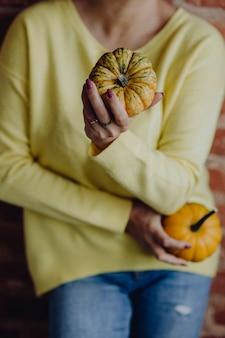 Donna in un maglione giallo che tiene le zucche nelle sue mani