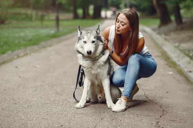 Donna in un parco di primavera che gioca con il cane carino