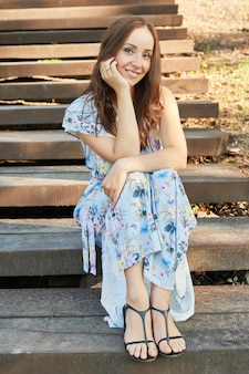 Donna in un parco si siede sulle scale