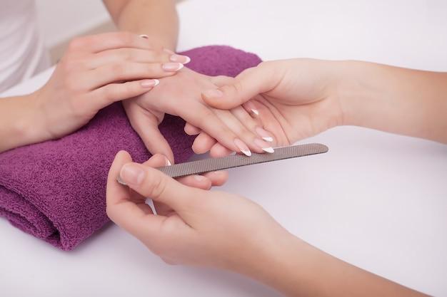 Donna in un salone del chiodo che riceve una manicure da un'estetista