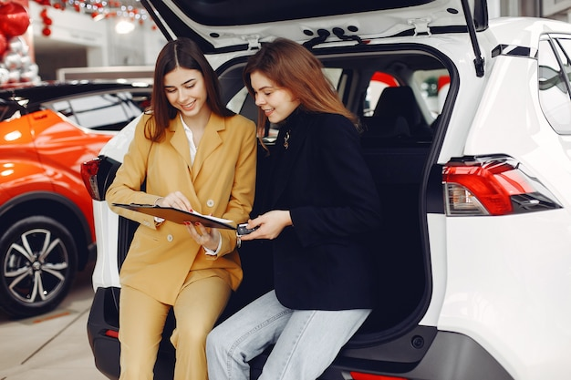 Donna in un salone di auto a parlare con l'assistente