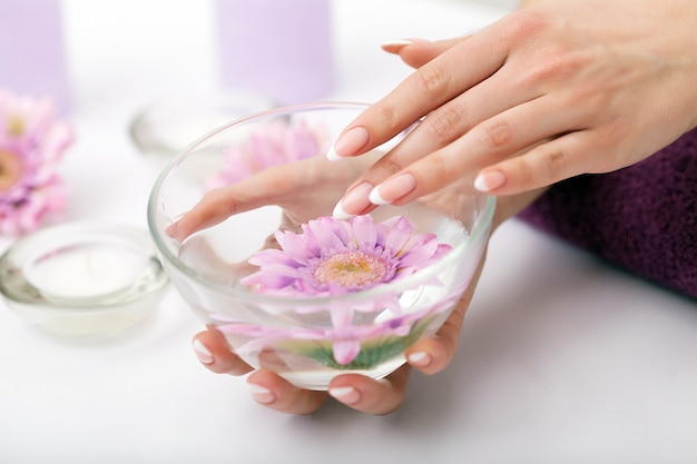 Donna in un salone per unghie che riceve una manicure da un'estetista