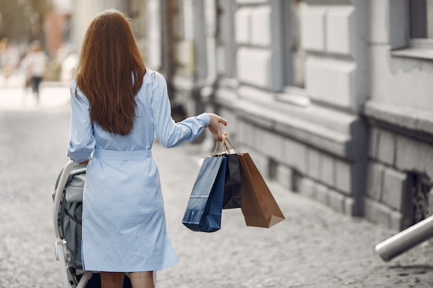 Donna in un vestito blu con il sacchetto della spesa e trasporto in una città