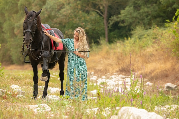 Donna in un vestito con un cavallo nero nella natura