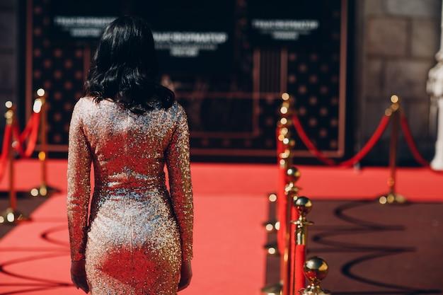 Donna in un vestito lussuoso su un tappeto rosso