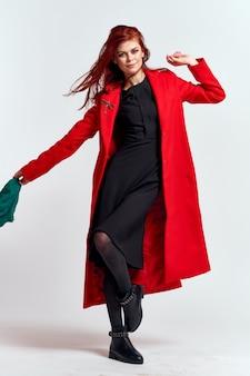 Donna in un vestito nero e cappotto rosso che posano su una parete leggera, modello