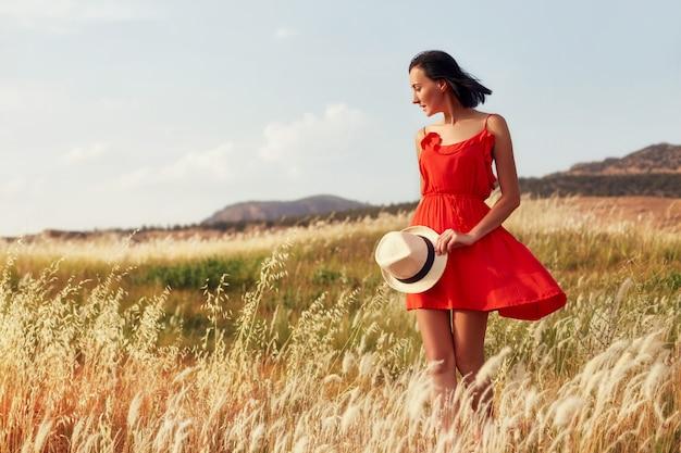Donna in un vestito rosso che cammina sull'estate del campo