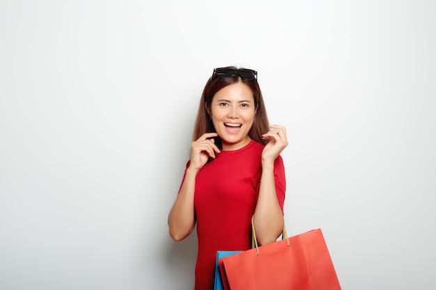 Donna in un vestito rosso che tiene un sacco di carta per acquistare
