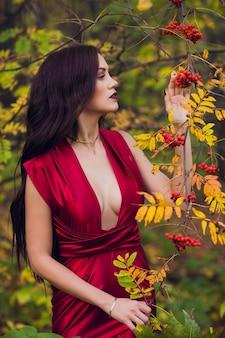 Donna in un vestito rosso lungo da solo nella foresta. favolosa e misteriosa immagine di una ragazza in una foresta oscura nel sole della sera. tramonto, la principessa si è persa.
