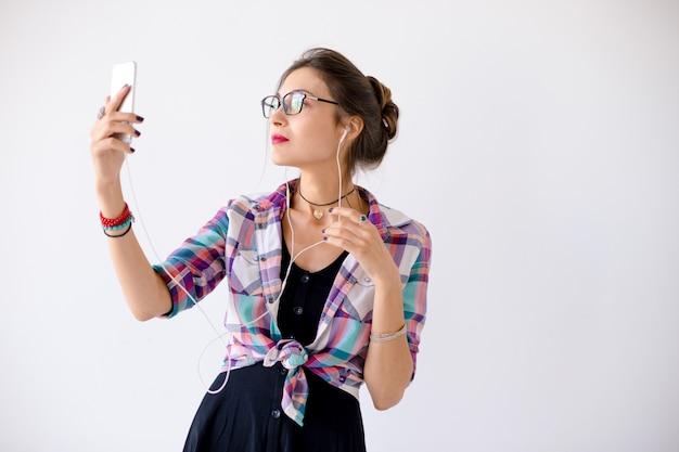 Donna in una camicia a quadri in occhiali plaing con le cuffie