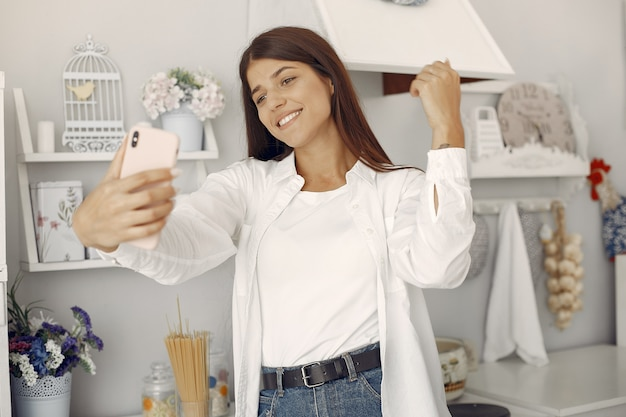 Donna in una camicia bianca che sta nella cucina e che fa un selfie