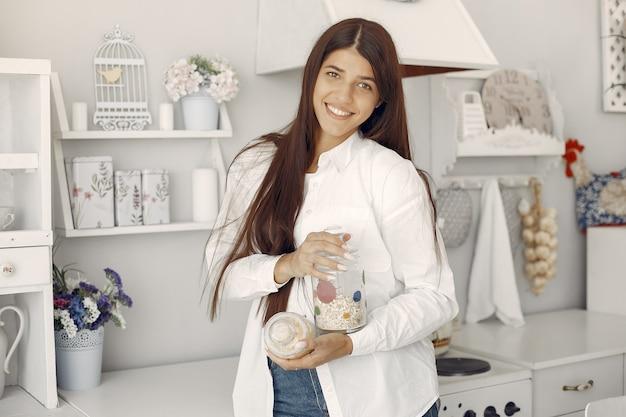 Donna in una camicia bianca in piedi nella cucina con farina d'avena