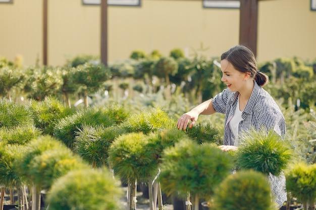 Donna in una camicia blu che lavora in una serra