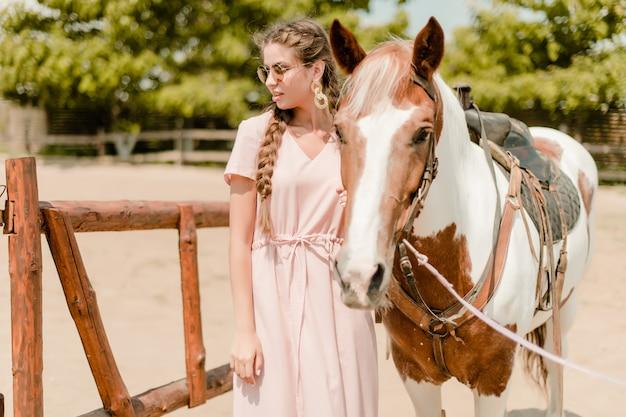 Donna in una campagna con un cavallo dal ranch