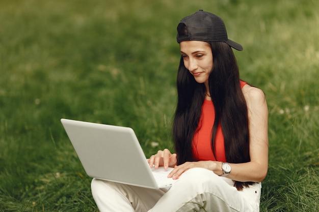 Donna in una città primaverile. signora con un laptop. ragazza seduta su un'erba.