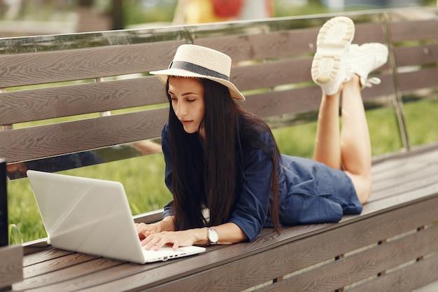Donna in una città primaverile. signora con un laptop. ragazza seduta su una panchina.