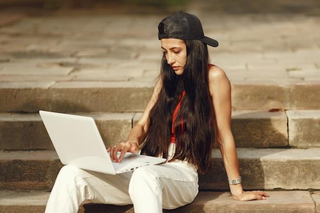 Donna in una città primaverile. signora con un laptop. ragazza seduta su una scala.