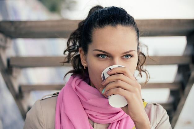 Donna in una giacca beige e una sciarpa rosa che beve caffè da una tazza di carta all'aperto