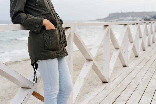 Donna in una giacca verde e blue jeans in piedi sul lungomare in legno vicino al mare