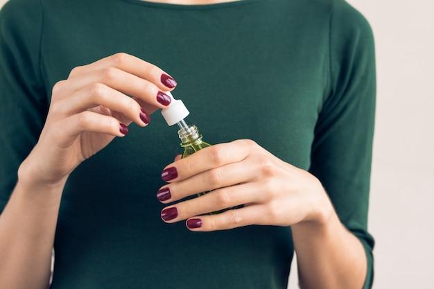 Donna in una maglietta verde e una manicure marrone rossiccio in possesso di un barattolo con un olio cosmetico