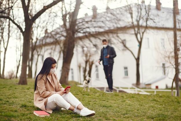 Donna in una maschera che si siede su un'erba