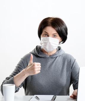Donna in una maschera protettiva alla scrivania.