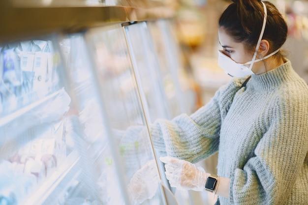Donna in una maschera protettiva in un supermercato