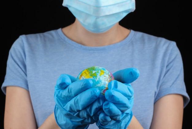 Donna in una mascherina protettiva medica, guanti che tengono globo su una parete nera. pandemic covid-19
