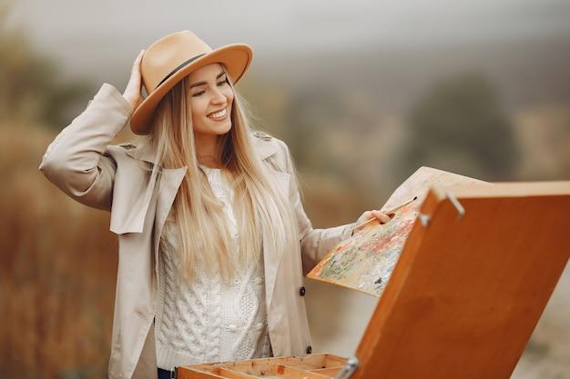 Donna in una pittura del cappotto marrone in un campo