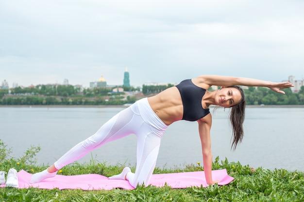 Donna in una posa yoga con il braccio raggiungendo in alto