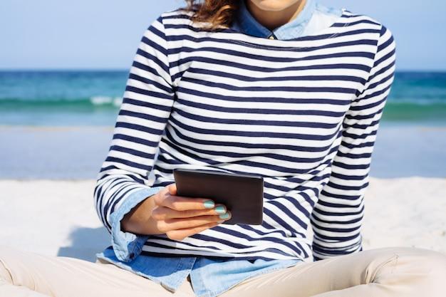 Donna in una t-shirt a righe seduto sulla spiaggia e leggendo un libro