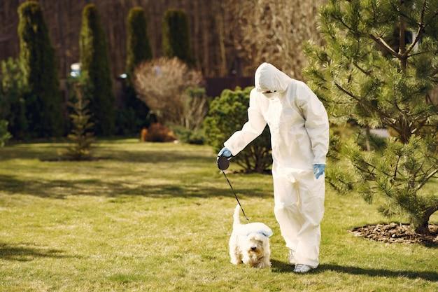 Donna in una tuta protettiva che cammina con un cane