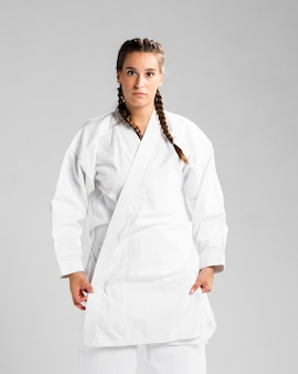 Donna in uniforme bianca e cintura nera che guarda l'obbiettivo