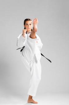 Donna in uniforme di arti marziali che esercita karatè