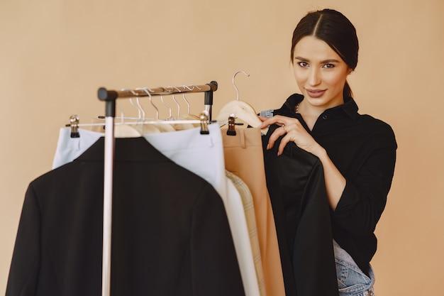 Donna in uno studio con molti vestiti