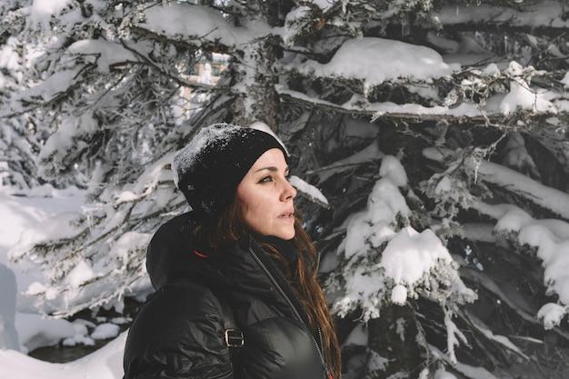 Donna in vestiti caldi sulla priorità bassa degli alberi di pino