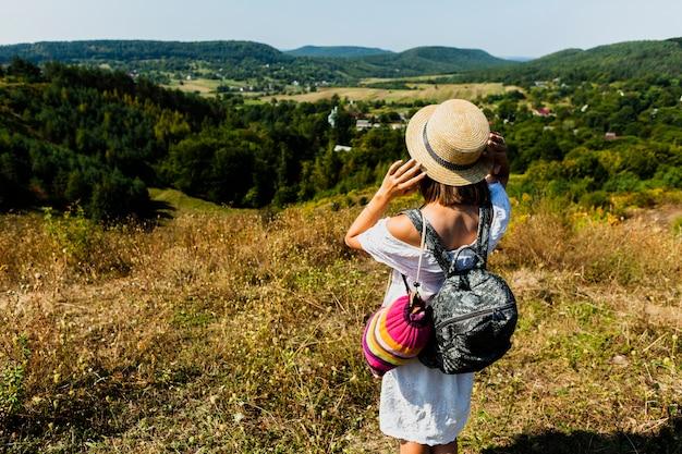 Donna in vestito bianco che prende una foto della foresta