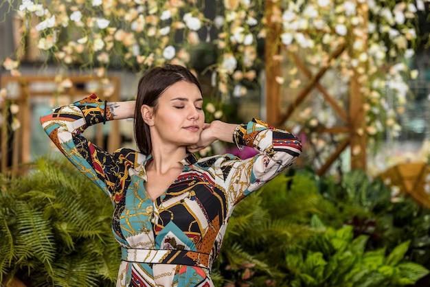 Donna in vestito che posa in serra