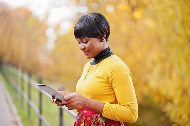 Donna in vestito giallo e rosso al parco dorato di caduta di autunno con la compressa a portata di mano