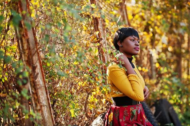 Donna in vestito giallo e rosso al parco dorato di caduta di autunno