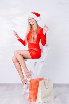 Donna in vestito rosso che si siede sulla sedia con il telefono