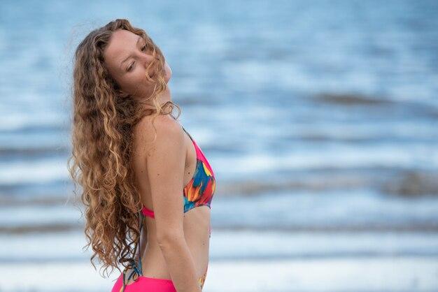 Donna in viaggio sulla spiaggia con i capelli biondi.