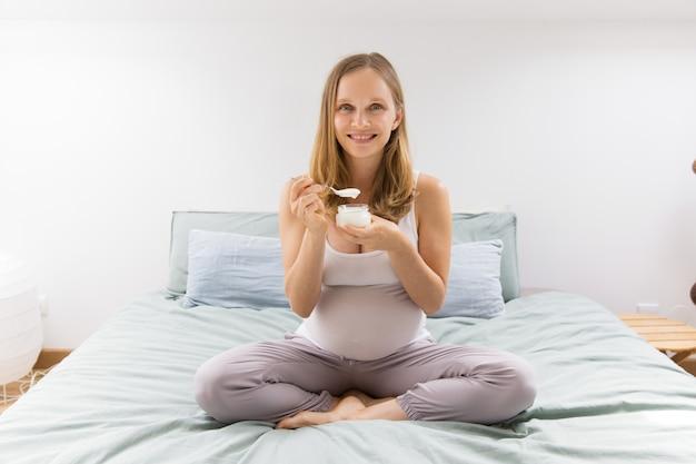 Donna incinta allegra che mantiene dieta sana