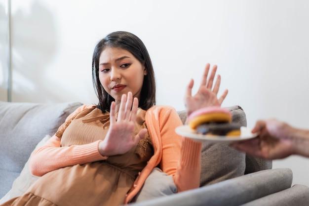 Donna incinta asiatica che rifiuta cibo spazzatura o cibo malsano come le ciambelle