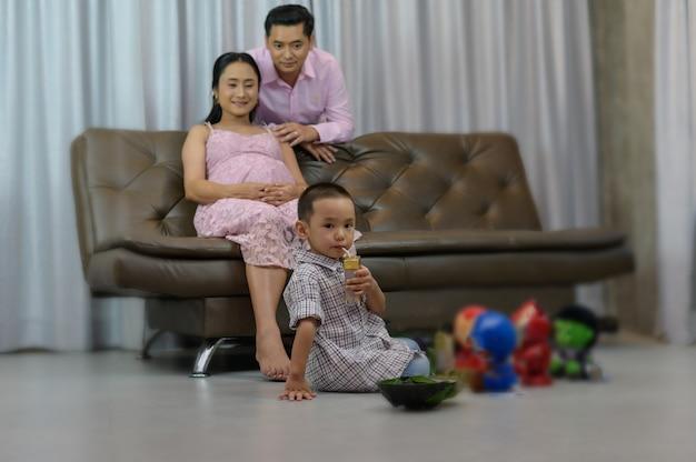 Donna incinta asiatica che si trova sul sofà e che esamina suo marito. giovane donna incinta con il marito che riposa in sofà